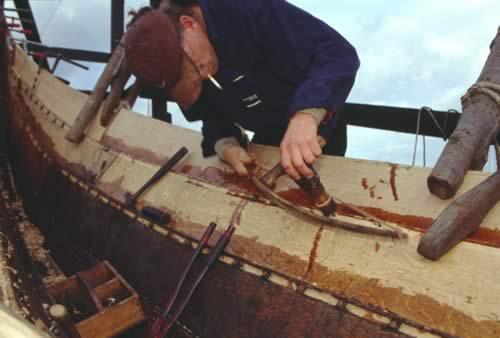 Bådebyggerne bruger et buebor til at borre huller i havhingstens skrog.