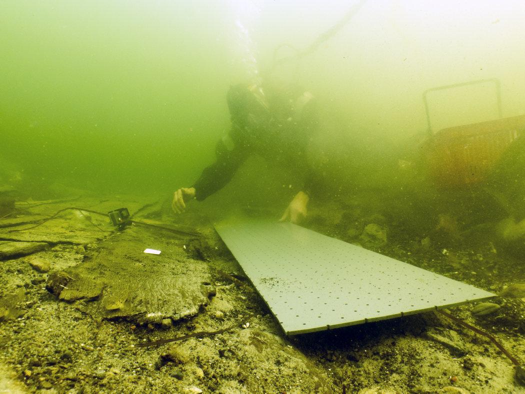 Marinarkæologen gør klar til at løfte de skrøbelige skibsdele ud af vandet på en tilpasset plade, som skibsdelen pakkes ind sammen med for at stabilisere og beskytte