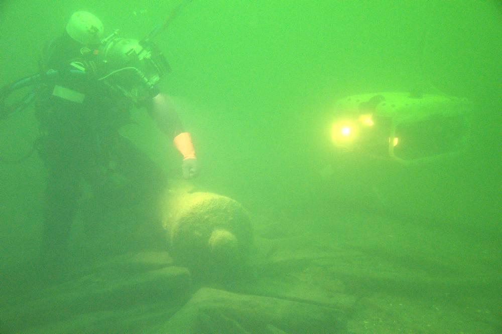 Martin, dykker fra JD-Contractor, forklarer dykkerlederen sine observationer via ROV'ens kamera. Morten Johansen, Vikingeskibsmuseet.
