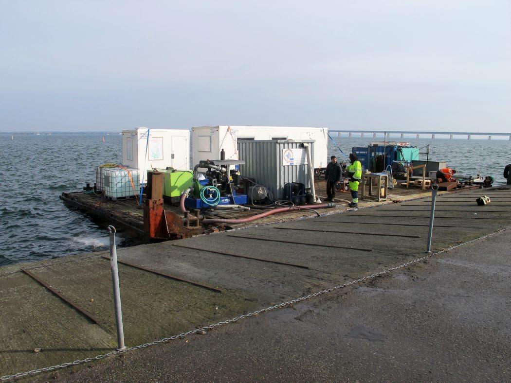 Dykkerflåden på 10x18 meter er tilrigget med skurvogn, dykkercontainer, generator mv. Herfra arbejder marinarkæologerne. Foto: Jørgen Dencker