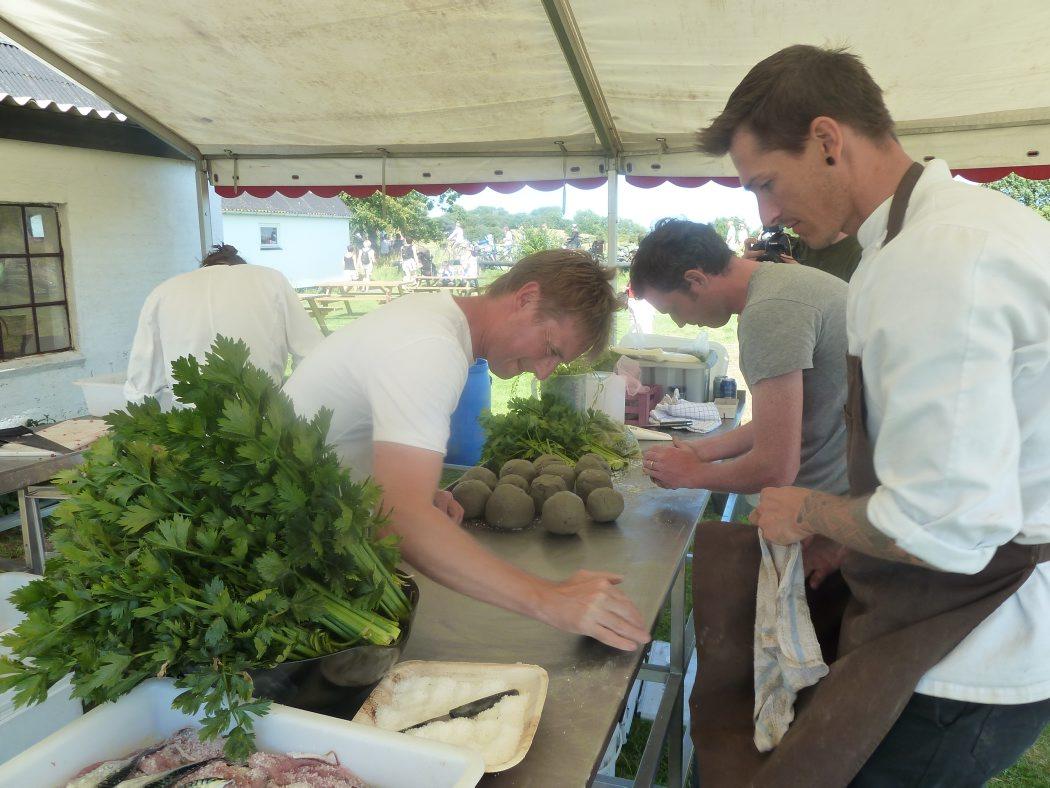 Friske selleri pakkes ind i ler, inden de lægges i bål i flere timer. Steven Lamb fra River Cottage (tv.), Kasper Gaard, Ilse Made (th.) og Gill Meller (bagerst).