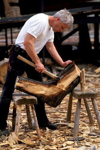 I forbindelse med rekonstruktionen af Skuldelevskibene arbejder Vikingeskibsmuseets bådebygger på et stykke krumvokset træ,