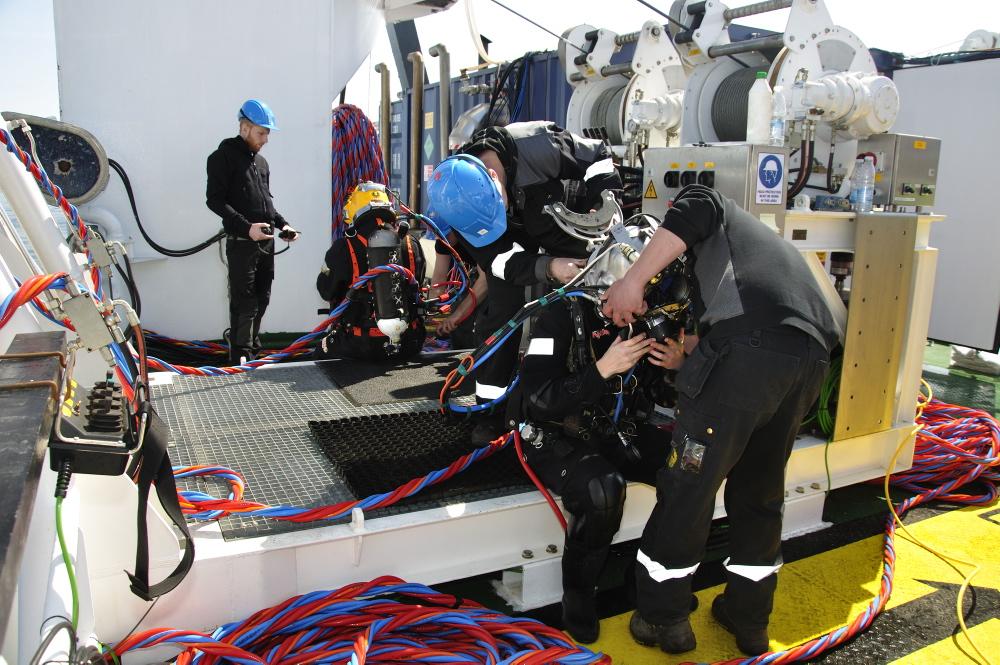 Torsdag d. 3/5: Den 17 kg tunge hjelm sættes på Athena af 2 dykkerassistenter. Foto: Morten Johansen