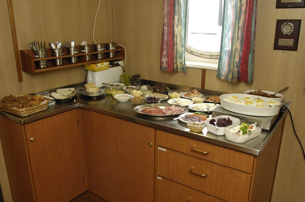 I messen er der rettet an til frokost. Om bord på VINA spiser man godt. Frokostbuffeten består af et udvalg af sild, pålæg, gode oste og en varm ret – her hakkebøf med spejlæg. Foto: Morten Johansen, Vikingeskibsmuseet.