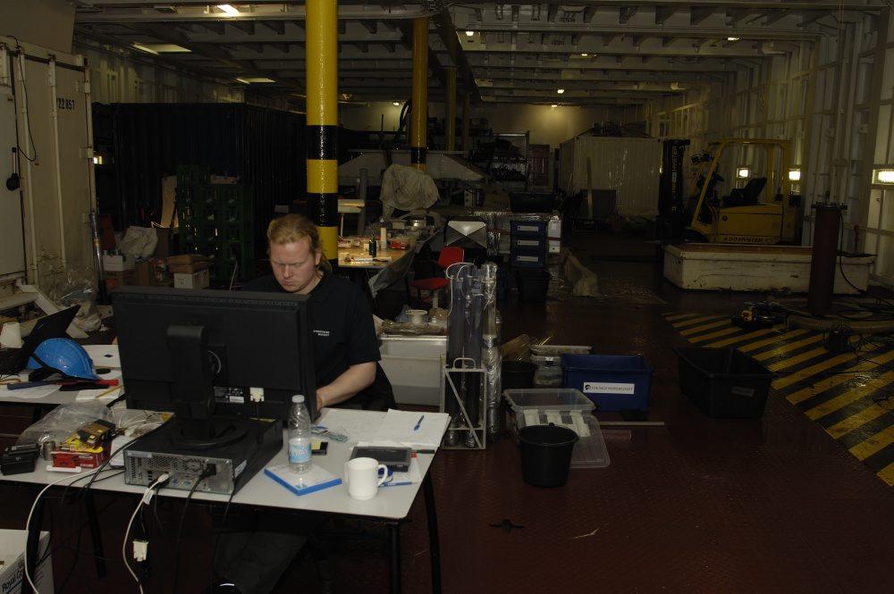 På en computer opstillet på mellemdækket er Anders i færd med at registrere de optagne genstande i databasen. Foto: Morten Johansen, Vikingeskibsmuseet.