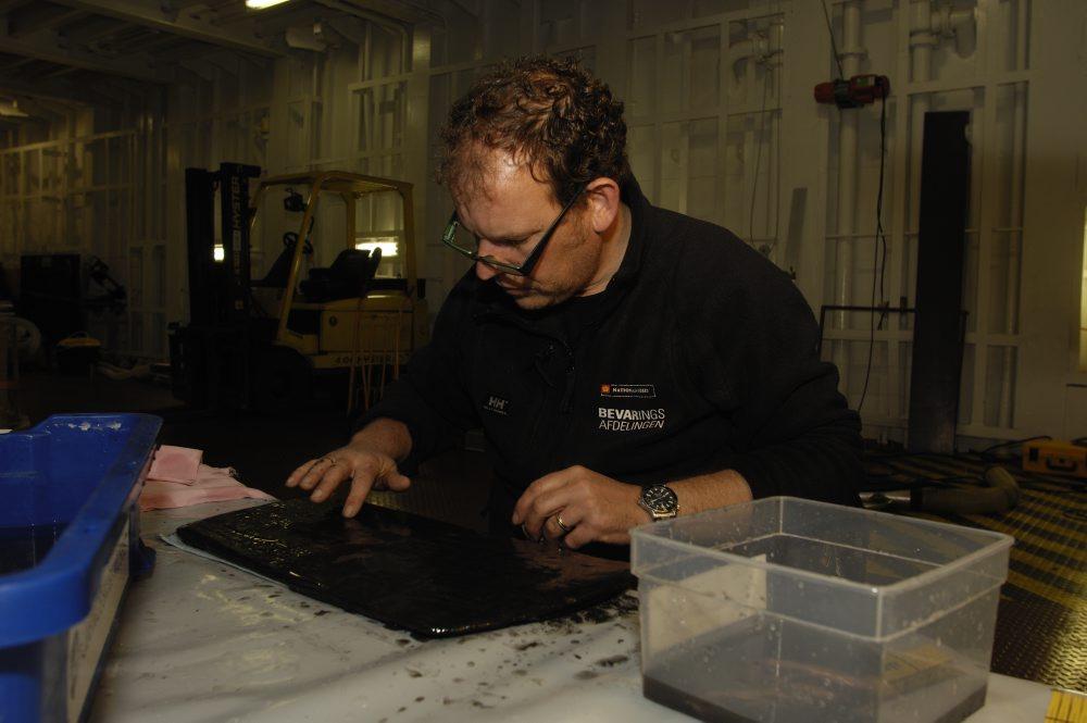 David Gregory, Nationalmuseets Bevaringsafdeling renser det sidste bundslam af låget til kobberkarret.  Foto: Morten Johansen, Vikingeskibsmuseet.