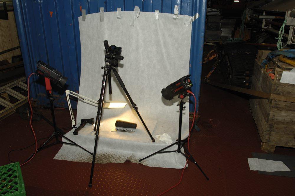 """Op af en container på """"mellemdækket"""" er det interimistiske fotostudie opstillet. Inden genstandene pakkes bliver de opmålt og fotograferet. Foto: Morten Johansen, Vikingeskibsmuseet."""