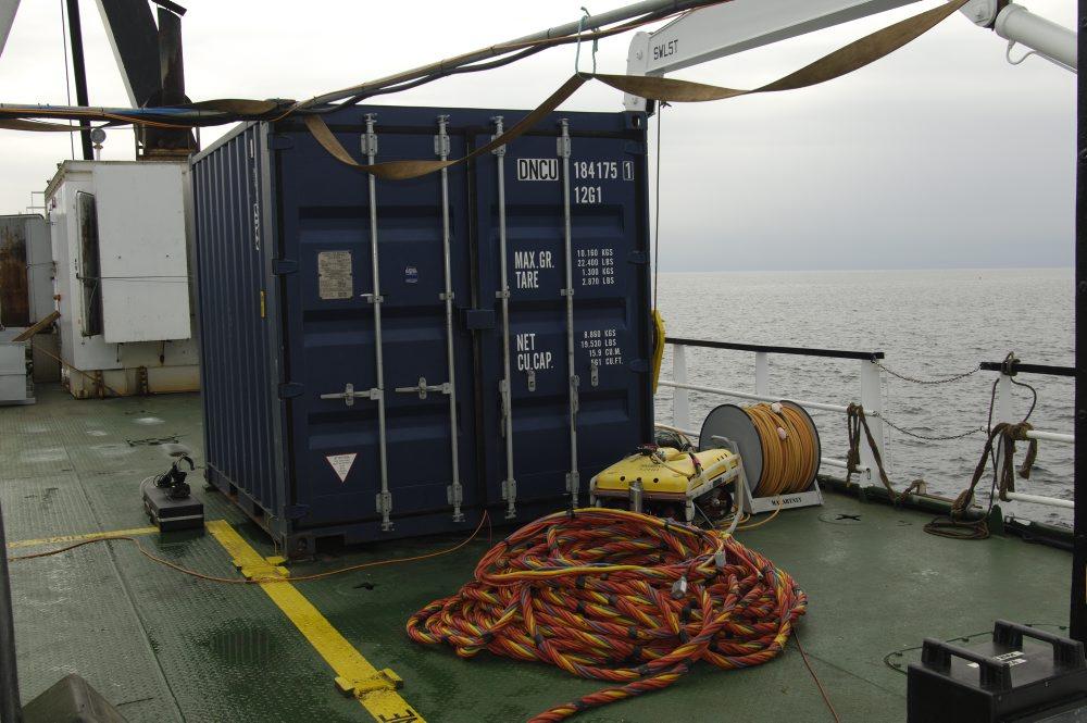 """Fra den fjerde container styres ROV'en (Remote Operated Vehicle), der er forsynet med et undervandsvideokamera. Det er også herfra marinarkæologerne kan følge dykkerne via hjelmkameraet og tale med dykkerne på """"dykkertelefonen"""". Her modtages ogs"""
