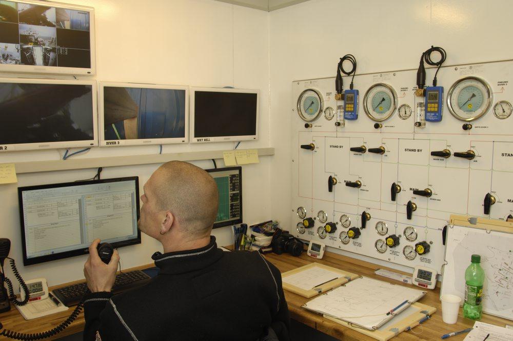 Inde i dykkerledercontaineren kan dykkerne følges på skærme og instrueres af projektlederen via dykkertelefonen. På panelet til højre aflæses og justeres luftblanding, lufttryk, dybde mv.  Foto: Morten Johansen, Vikingeskibsmuseet.