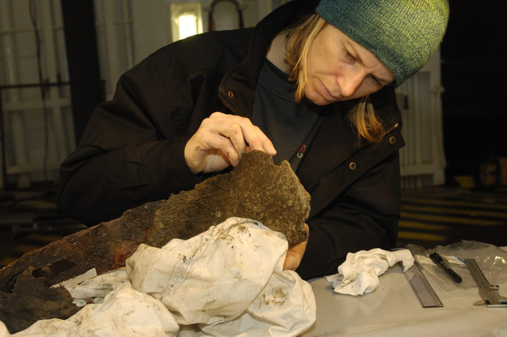 """I øverste lastrum, kaldet """"mellemdækket,"""" er Athena i gang med at fjerne tangrester og begroning fra kobberkarret. Foto: Morten Johansen, Vikingeskibsmuseet."""