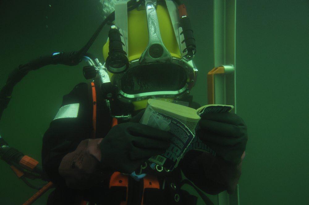 Athena læser i dykkerkurven mens hun dekomprimerer en halv time på 6 meters dybde. Foto: Morten Johansen, Vikingeskibsmuseet.