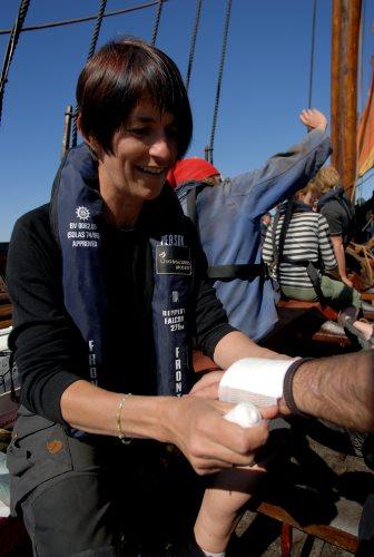 Sygeplejersken Susanne lægger forbinding om håndleddet på et besætningsmedlem. Foto: Werner Karrasch, Vikingeskibsmuseet