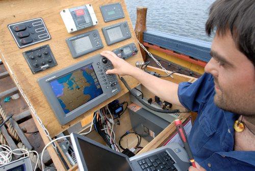 Martin ved navigationskassen med GPS, kortplodder, VHF radio ect. Foto: Werner Karrasch, Vikingeskibsmuseet